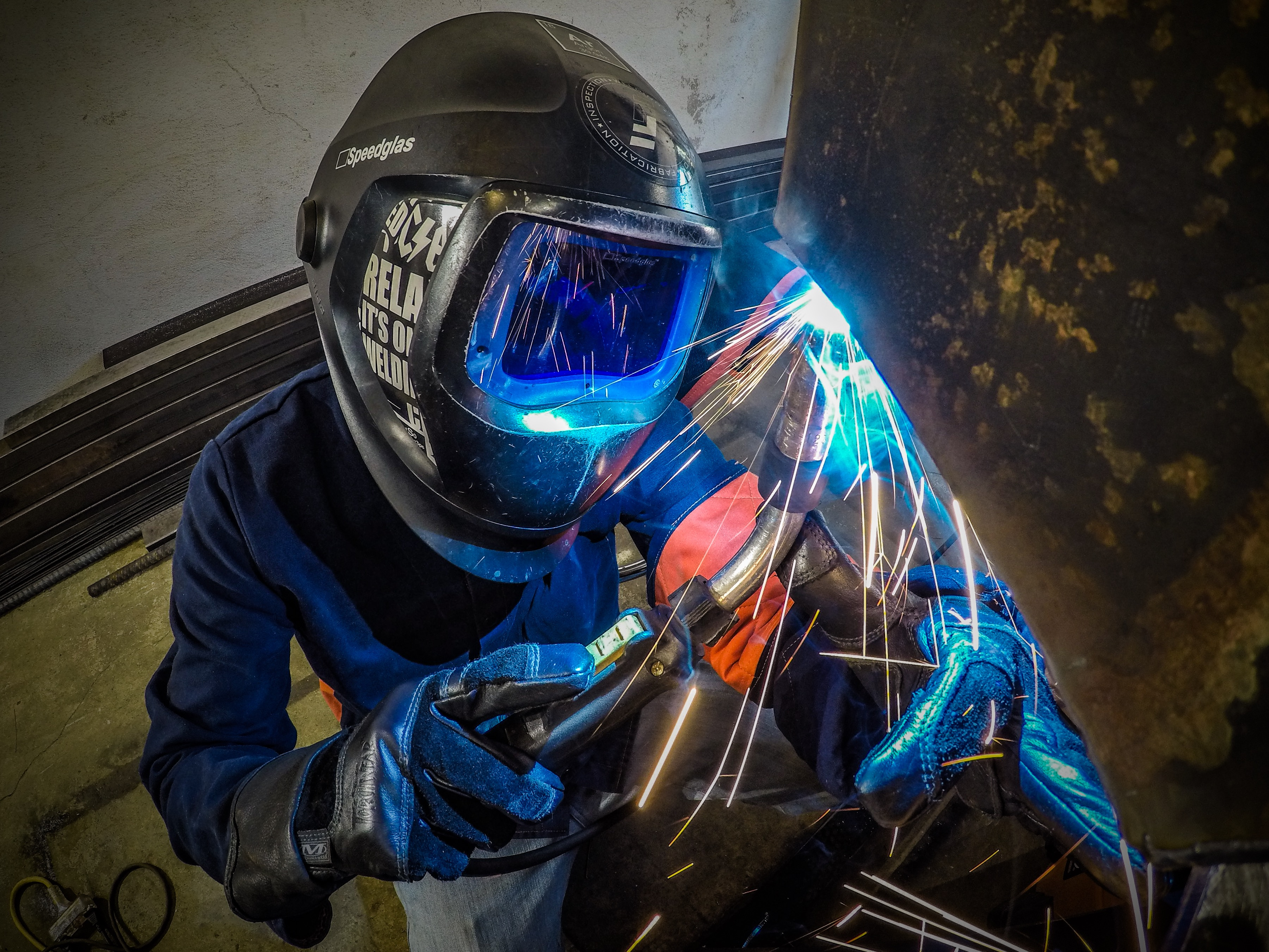 Man Doing Mig Welding Overhead on an Old Metal Above him