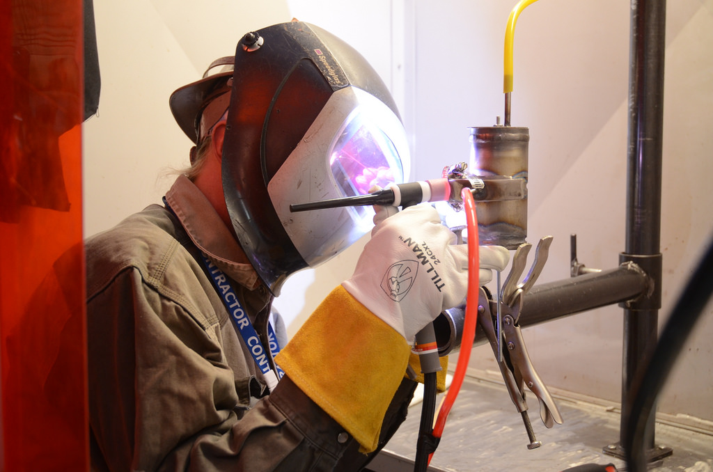 Man Learning how to weld titanium pipes through a Community College for Welding Certification