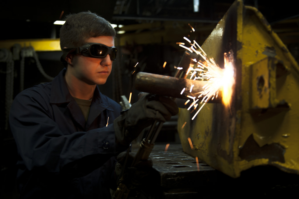 Man cuts a piece of metal with an acetylene cutting torch