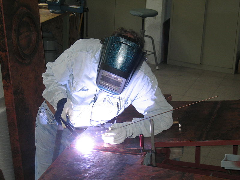 Man performing TIG welding of a monumental sculpture