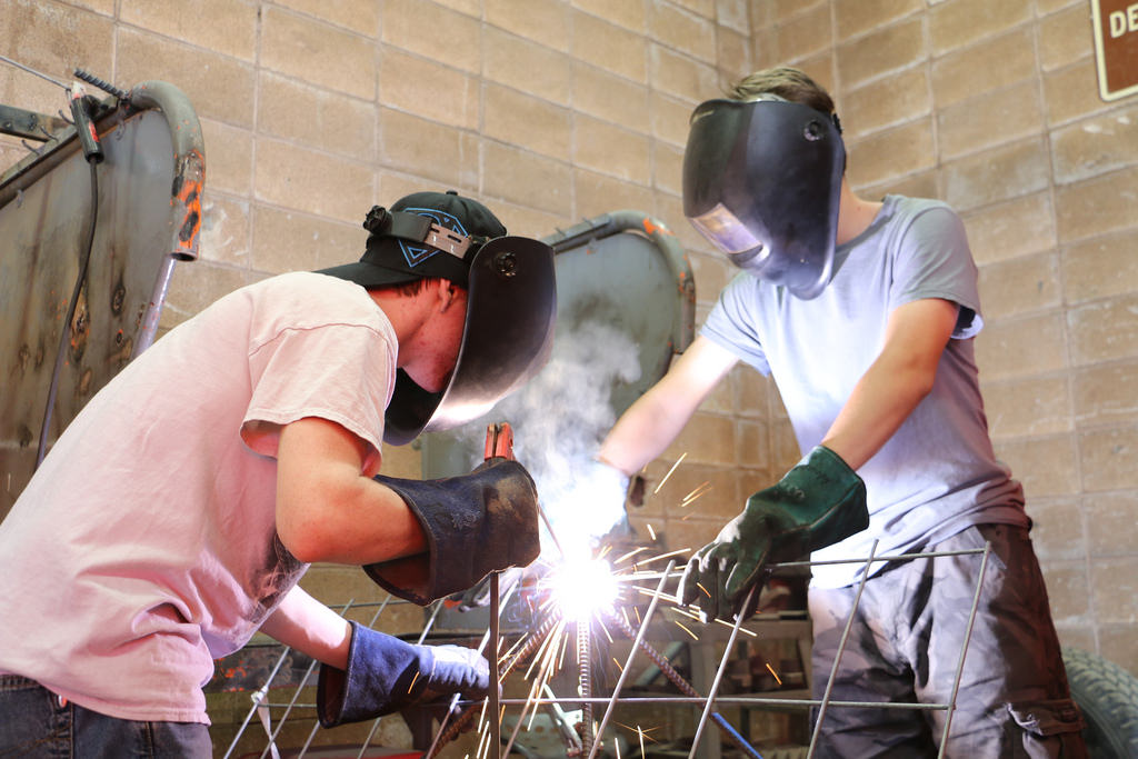 Two Teenager Men Wearing Welding Safety Gears and Helping Each other on a Welding Class