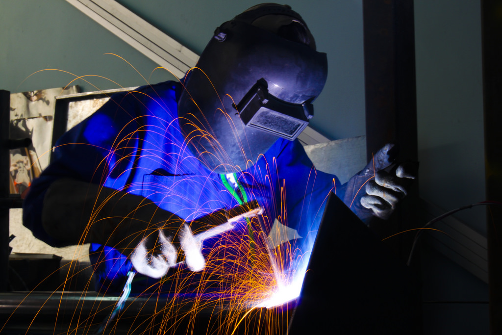 Fully-Geared Welder at a Workshop while doing Stick Welding on a Workshop with sparks