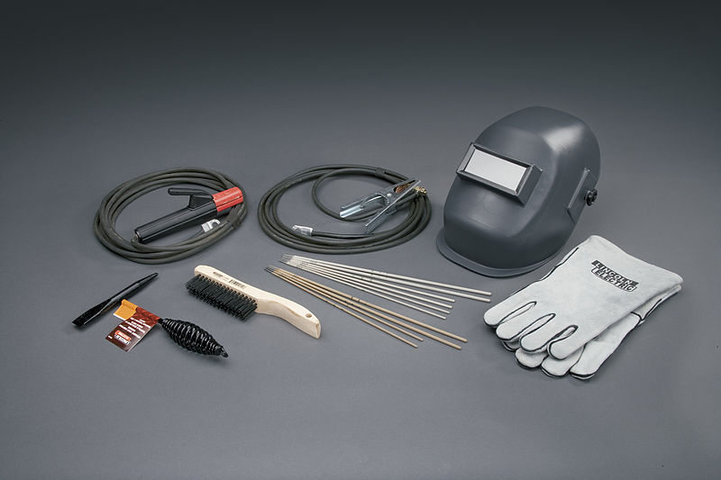 Various accessories for Stick Welding on a Workshop with helmet, rods, brush, voltage wires, and more
