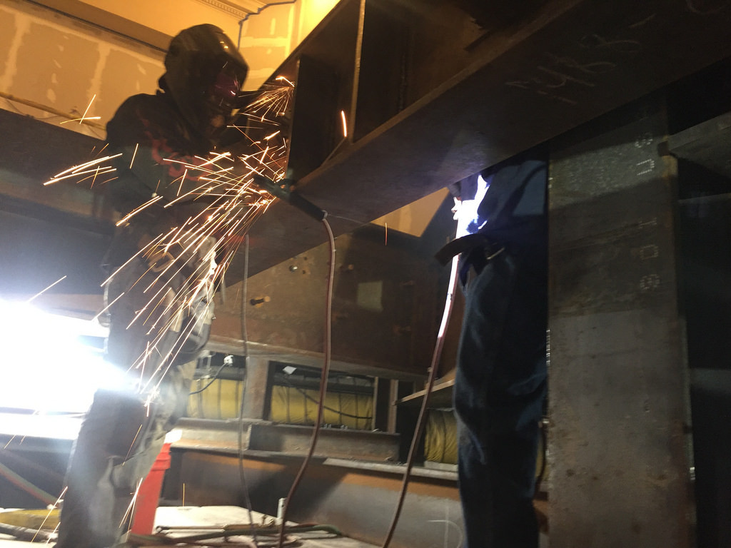 Fully-Geared Men Doing Flux Core Welding on a structural support beams in the Grand Central Terminal Biltmore Room