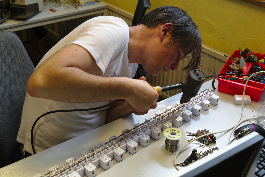 Man Using a couple of filler metal welding rods and to solder the adapters onto that baseuses Welding Rod Chart as a guide