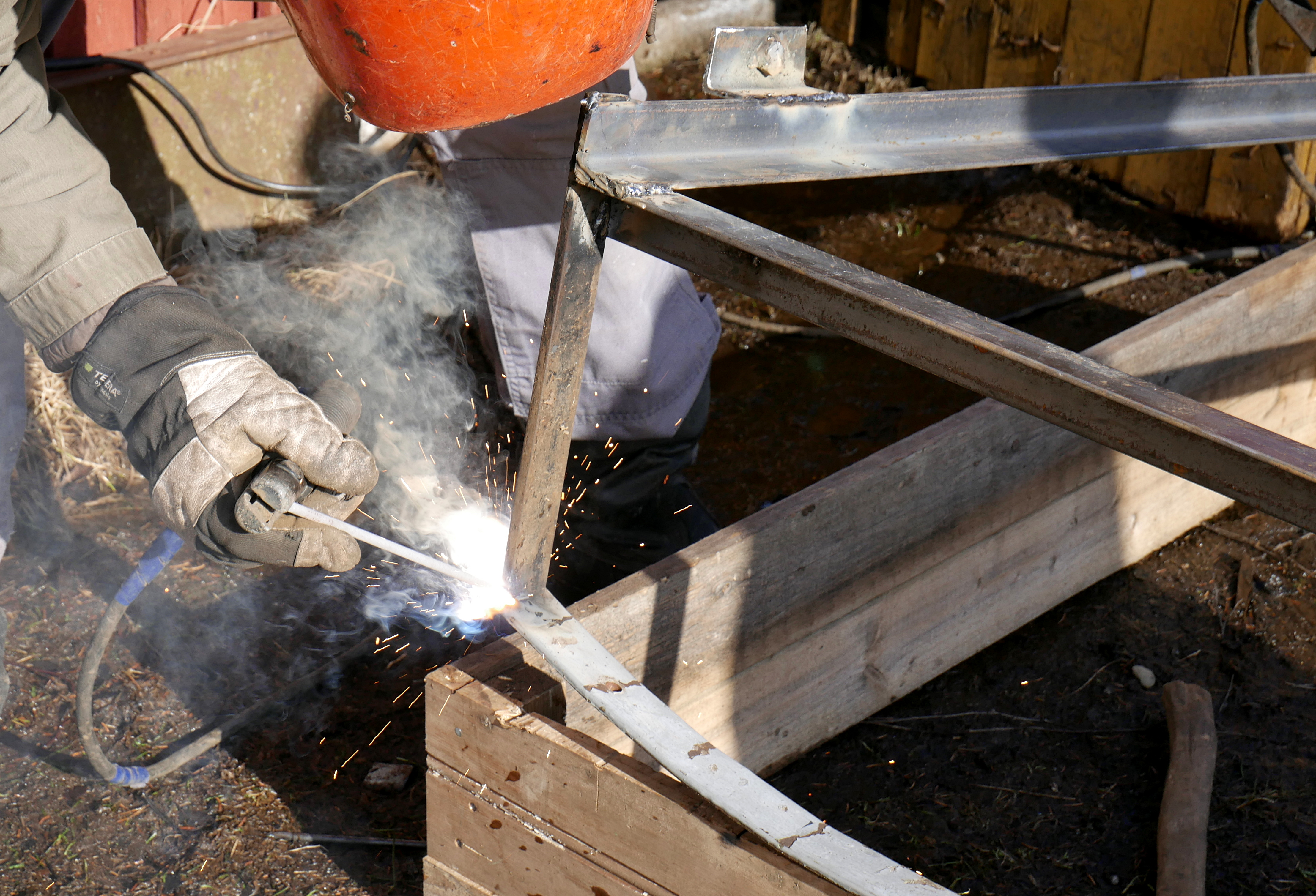 Welder doing Arc welding on metal frames with a wood bases who uses a Welding Rod Chart