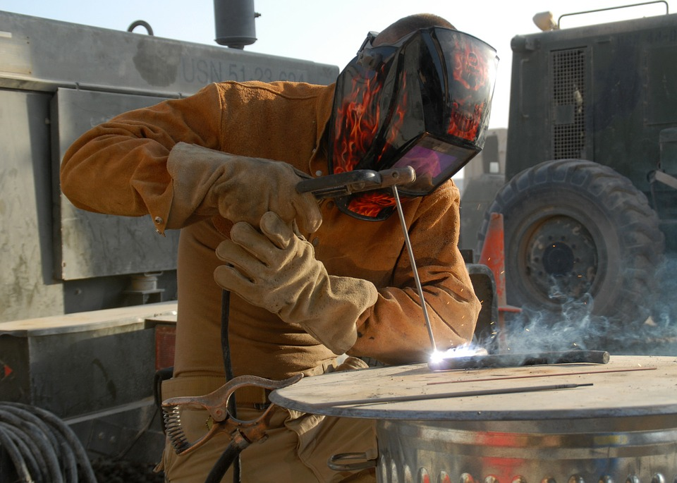Welder with helmet Using filler metal welding rodswho uses Welding Rod Chart as a guide