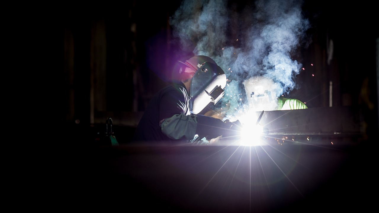 Two person wearing a welding mask while welding a metal